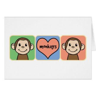 Monos lindos del clip art del dibujo animado con tarjeta pequeña