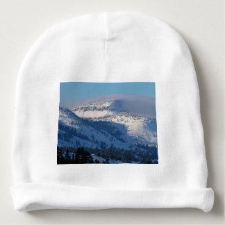 Montañas con nieve que sopla gorrito para bebe