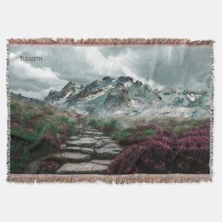 Montañas románticas con el camino y las flores de manta