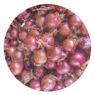 Montón de cebollas rojas en mercado plato