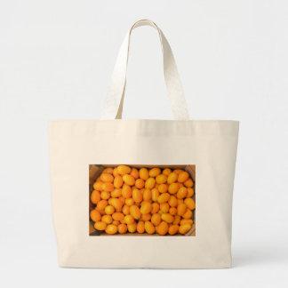 Montón de kumquats anaranjados en caja de cartón bolsa de tela grande