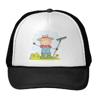 Muchacho del granjero con un rastrillo en hierba gorra