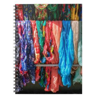 Muchas bufandas coloridas que cuelgan en el cuaderno