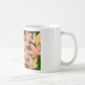 Muchas hojas de arce coloridas del otoño en hierba taza de café