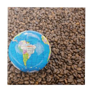Muchos granos de café enteros con el globo de azulejo