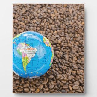 Muchos granos de café enteros con el globo de placa expositora