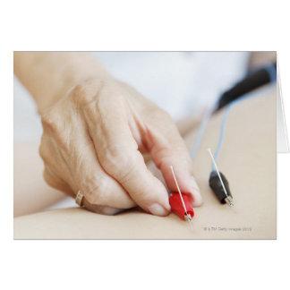 Mujer asiática (70-75 años) que pone rojo y tarjeta de felicitación