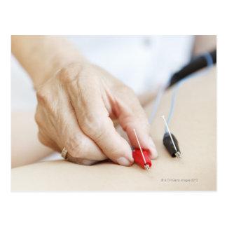 Mujer asiática (70-75 años) que pone rojo y tarjetas postales
