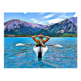 Mujer Canoeing o kayaking por la postal del océano