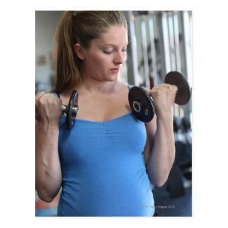 mujer embarazada que ejercita en el club de salud postal