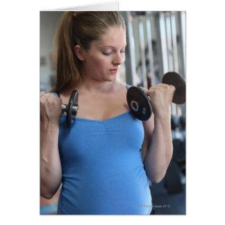 mujer embarazada que ejercita en el club de salud tarjeton