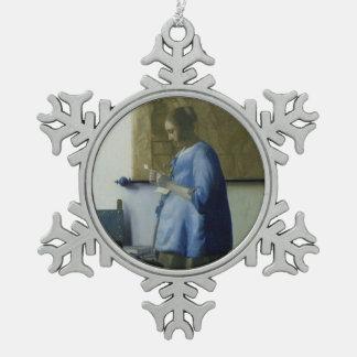 Mujer embarazada que lee una letra adorno de peltre tipo copo de nieve