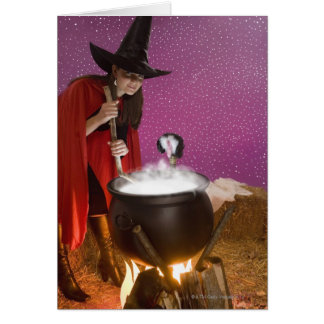 Mujer en el traje de la bruja que revuelve la cald felicitación