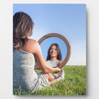 Mujer en la naturaleza que ve su imagen de espejo placa expositora