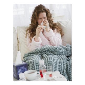Mujer enferma en el sofá postal