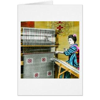 Mujer japonesa del vintage que usa un molino de tarjeta de felicitación