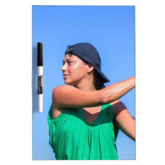 Mujer joven con el bate de béisbol y el casquillo pizarra blanca