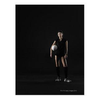 Mujer joven que lleva a cabo el voleibol, retrato postal