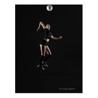 Mujer joven que salta para golpear el voleibol, postal
