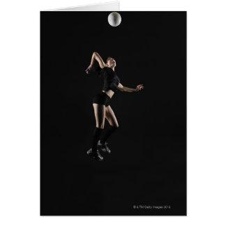 Mujer joven que salta para golpear el voleibol, tarjeta de felicitación