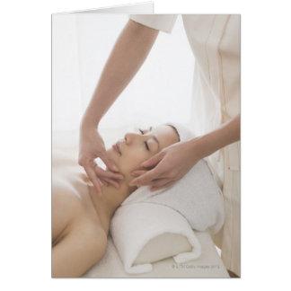 Mujer joven que tiene masaje facial felicitación