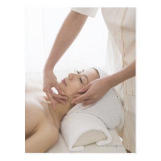 Mujer joven que tiene masaje facial tarjeta postal