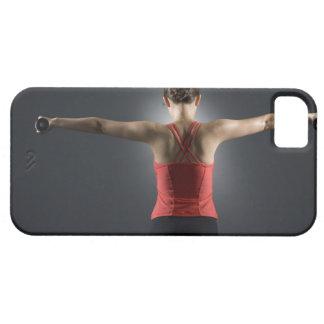 Mujer joven que usa las pesas de gimnasia, vista p iPhone 5 protectores