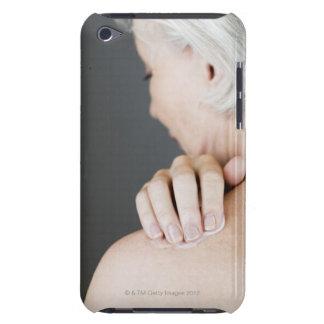 Mujer mayor que aplica la crema hidratante a ella funda iPod