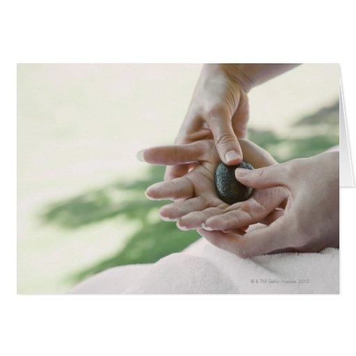Mujer que consigue masaje de la mano con la piedra tarjeta