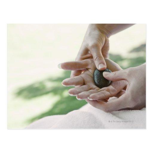 Mujer que consigue masaje de la mano con la piedra tarjetas postales