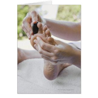 Mujer que consigue masaje del pie con la piedra ca felicitación