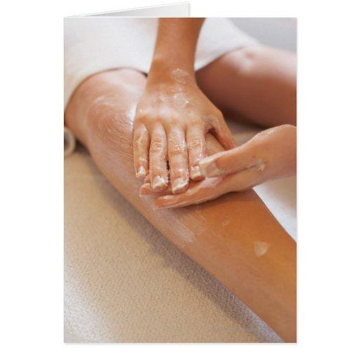 Mujer que recibe masaje de la pierna con la loción felicitacion