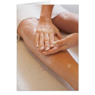 Mujer que recibe masaje de la pierna con la loción tarjeta de felicitación