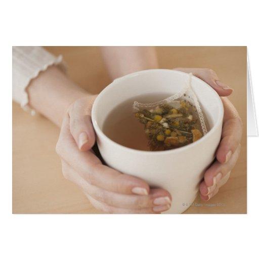 Mujer que sostiene la taza con té de manzanilla tarjeta