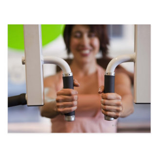 Mujer que usa la máquina del ejercicio en gimnasio tarjeta postal