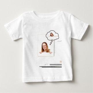 Mujer rubia que piensa en el tablero blanco camiseta de bebé