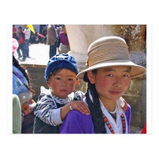 Mujer tibetana con el niño postal