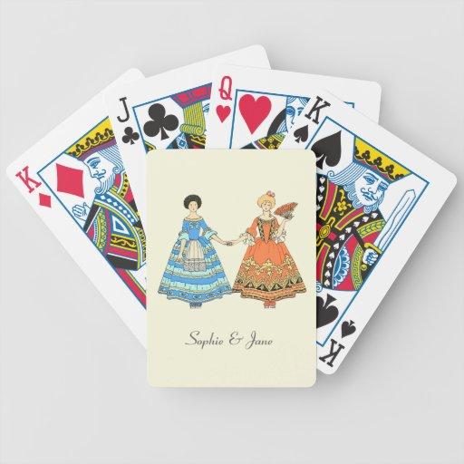 Mujeres en los trajes azules y rojos que llevan a baraja cartas de poker