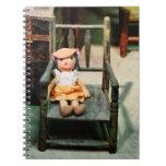 Muñeca de trapo en silla libros de apuntes con espiral