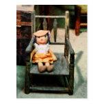 Muñeca de trapo en silla postal