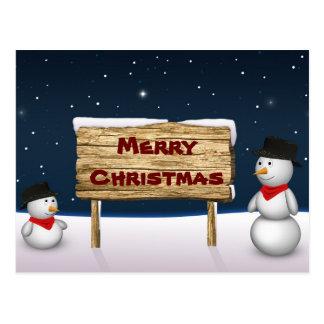 Muñecos de nieve lindos con una muestra de madera  tarjeta postal