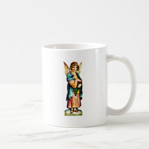 Navidad que saluda con un ángel que se coloca con  tazas de café