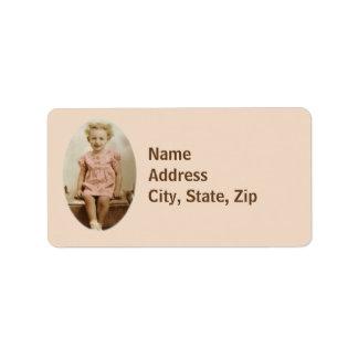 Niña del vintage en etiquetas de dirección rosadas