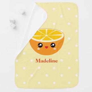 Niña feliz femenina linda del naranja dulce de mantas de bebé