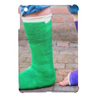 Niño derecho con dos piernas coloridas del yeso