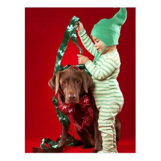 Niño pequeño que adorna un perro postal