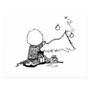 Niño que adorna el árbol de navidad - postal