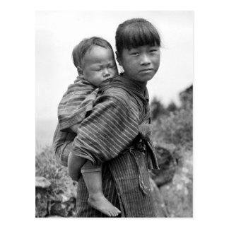 Niño que lleva del chica asiático en ella detrás postal
