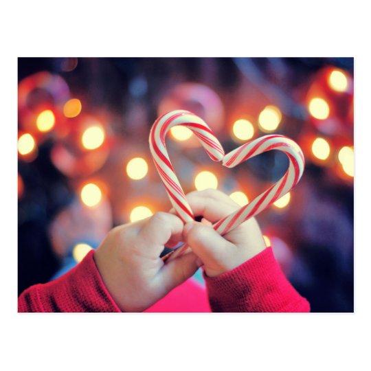 Niño que sostiene el caramelo del navidad con postal