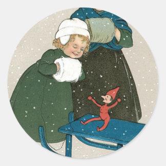 Niños con el trineo en navidad en la nieve pegatina redonda